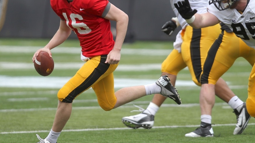 Iowa quarterback C.J. Beathard eludes tacklers during their spring NCAA college football game at Kinnick Stadium in Iowa City on Saturday, April 27, 2013. (AP Photo/Iowa City Press-Citizen, Benjamin Roberts )  NO SALES