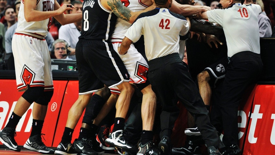 Referee Eric Lewis (42) and referee Ron Garretson (10) try to break up a scuffle between Chicago Bulls' Nate Robinson and Brooklyn Nets' C.J. Watson during the first half in Game 4 of their first-round NBA basketball playoff series Saturday, April 27, 2013, in Chicago. (AP Photo/Jim Prisching)
