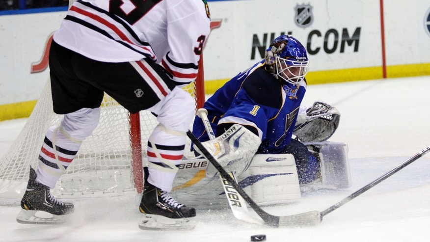 St. Louis Blues goalie Brian Elliott (1) deflects a shot from Chicago Blackhawks' Jimmy Hayes (39) in the first period of an NHL hockey game, Saturday, April 27, 2013 in St. Louis. (AP Photo/Tom Gannam)