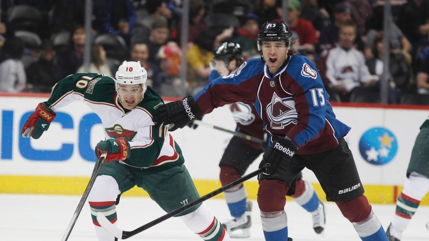 Minnesota Wild right wing Devin Setoguchi, left, pursues the puck along with Colorado Avalanche right wing PA Parenteau in the first period of an NHL hockey game in Denver on Saturday, April 27, 2013. (AP Photo/David Zalubowski)