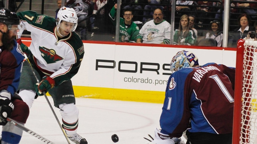 Minnesota Wild center Matt Cullen, left, directs a shot at Colorado Avalanche goalie Semyon Varlamov, of Russia, in the first period of an NHL hockey game in Denver on Saturday, April 27, 2013. (AP Photo/David Zalubowski)