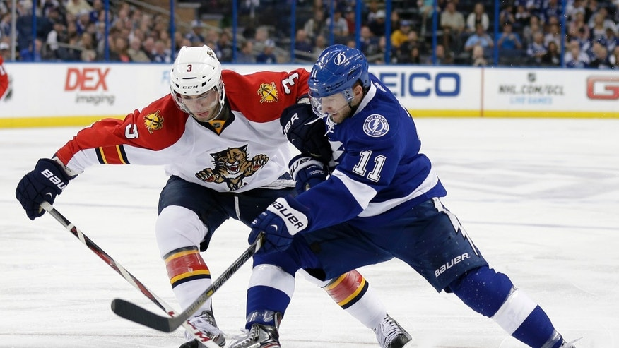 Florida Panthers defenseman T.J. Brennan (3) battles with Tampa Bay Lightning center Tom Pyatt (11) for the puck during the second period of an NHL hockey game Saturday, April 27, 2013, in Tampa, Fla. (AP Photo/Chris O'Meara)