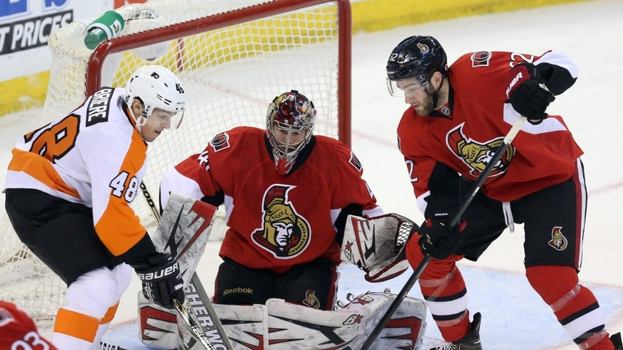 Ottawa Senators' Eric Gryba (62) and Philadelphia Flyers' Danny Briere (48) fight for possession of the puck as Senators goaltender Craig Anderson (41) looks on during second period NHL hockey action in Ottawa Saturday April 27, 2013.  (AP Photo/The Canadian Press, Fred Chartrand)