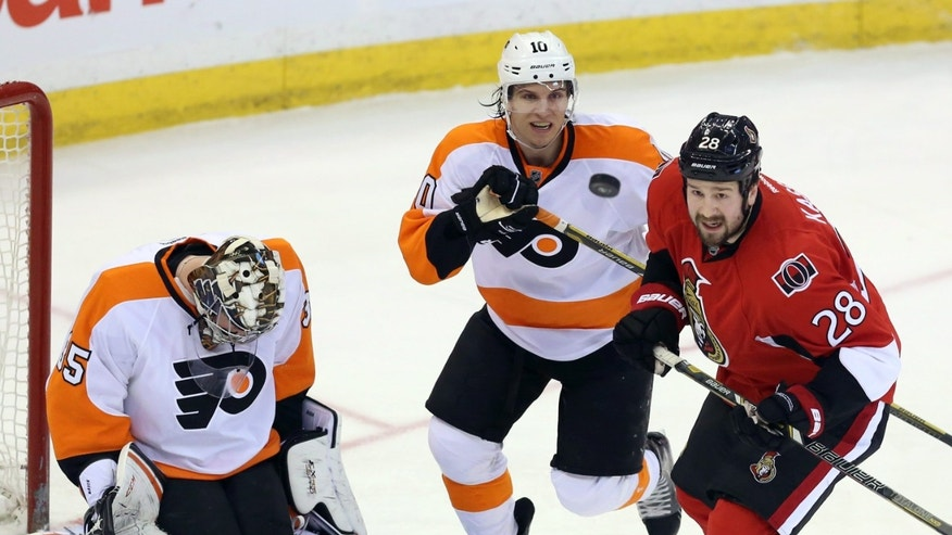 Ottawa Senators' Matt Kassian (28) and Philadelphia Flyers Brayden Schenn (10)keep their eyes on a flying puck as Flyers goaltender Steve Mason (35) looks for the puck during first period NHL hockey action in Ottawa Saturday April 27 2013.  (AP Photo/The Canadian Press, Fred Chartrand)