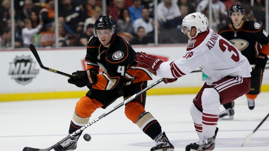 Anaheim Ducks defenseman Cam Fowler, left, battles Phoenix Coyotes left wing Rob Klinkhammer for the puck during the second period of an NHL hockey game in Anaheim, Calif., Saturday, April 27, 2013. (AP Photo/Chris Carlson)