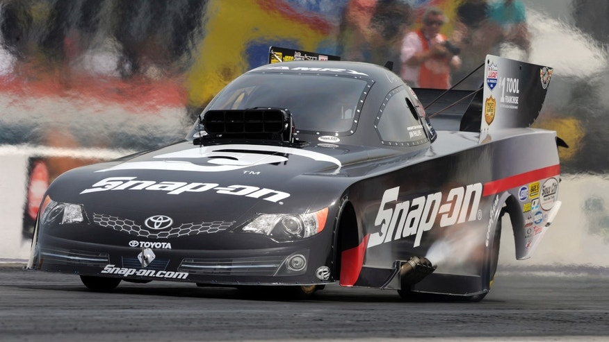 In this photo provided by NHRA, Cruz Pedregon powers down the drag strip in his Snap-on Tools Toyota Camry en route to his second Funny Car victory of the season in the final round of the O'Reilly Auto Parts NHRA SpringNationals auto race, Sunday, April 28, 2013, at Royal Purple Raceway in Baytown, Texas. (AP Photo/NHRA, Jerry Foss)