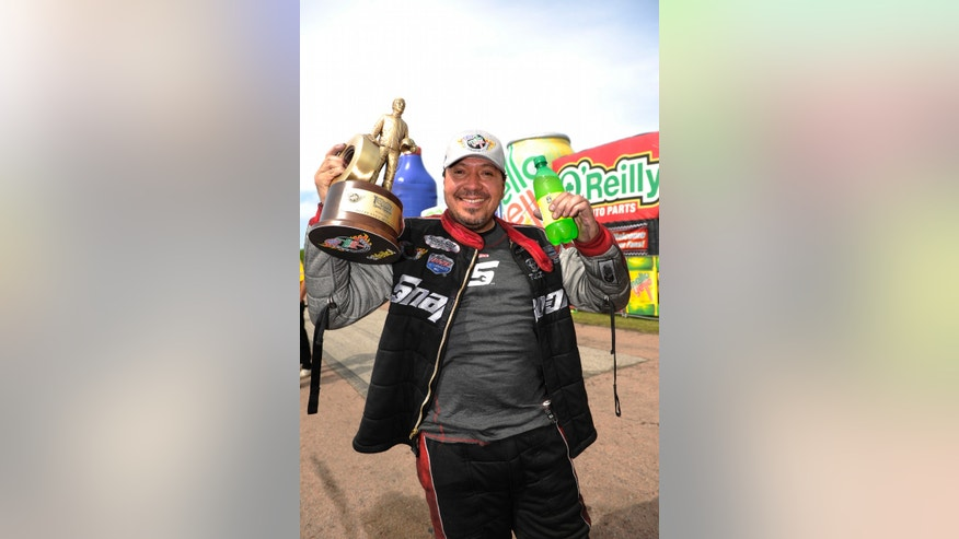 In this photo provided by NHRA, Cruz Pedregon poses while celebrating his second Funny Car victory of the season in the final round of the O'Reilly Auto Parts NHRA SpringNationals auto race, Sunday, April 28, 2013, at Royal Purple Raceway in Baytown, Texas. (AP Photo/NHRA, Jerry Foss)