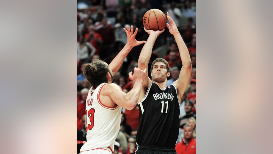 Chicago Bulls' Joakim Noah, left, tries to  block the shot of Brooklyn Nets' Brook Lopez (11) during the second overtime in Game 4 of their first-round NBA basketball playoff series Saturday, April 27, 2013, in Chicago. The Bulls won 142-134 in three overtimes. (AP Photo/Jim Prisching)