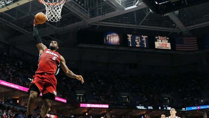 Miami Heat's LeBron James (6) dunks against the Milwaukee Bucks during the first half of Game 4 in a first-round NBA basketball playoff series, Sunday, April. 28, 2013, in Milwaukee. Giving chase are Bucks' Brandon Jennings (3), Ersan Ilyasova (7), of Turkey, and Heat's Shane Battier. (AP Photo/Jeffrey Phelps)