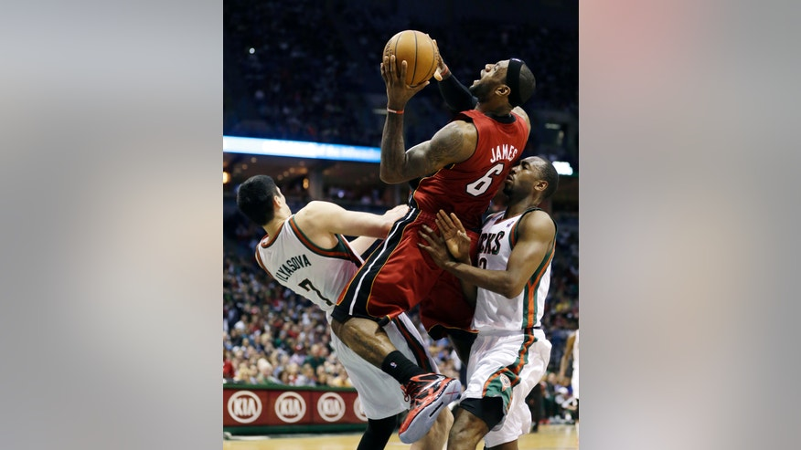 Miami Heat's LeBron James (6) drives against Milwaukee Bucks' Ersan Ilyasova, left, and Luc Richard Mbah a Moute during the first half of Game 4 in a first-round NBA basketball playoff series, Sunday, April. 28, 2013, in Milwaukee. (AP Photo/Jeffrey Phelps)