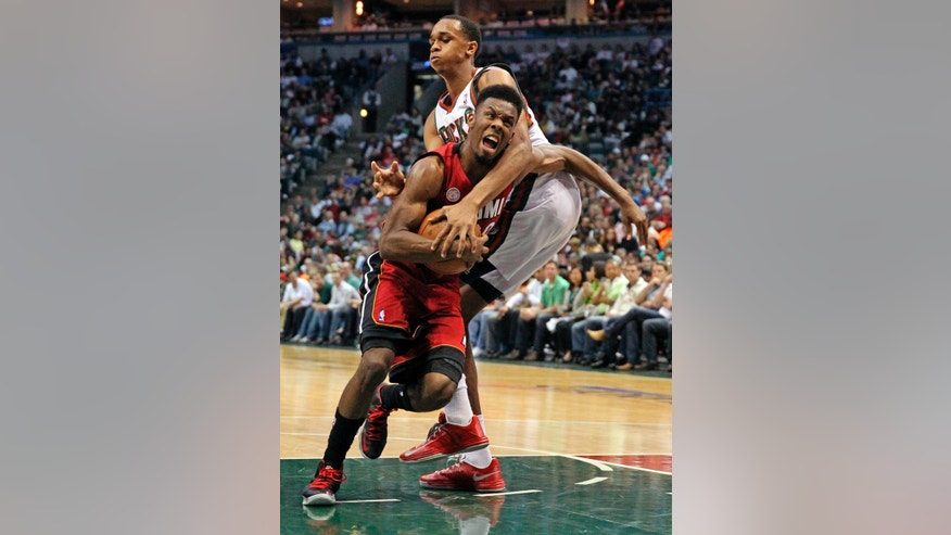 Milwaukee Bucks' John Henson fouls Miami Heat's Norris Cole, left, during the second quarter of Game 4 in their first-round NBA basketball playoff series, Sunday, April 28, 2013, in Milwaukee. (AP Photo/The Miami Herald, Al Diaz) MAGS OUT.