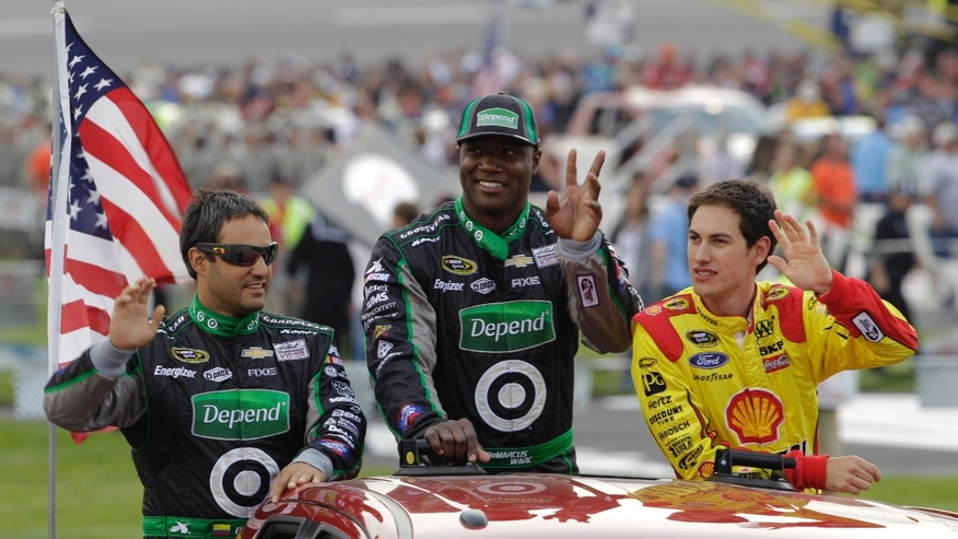 Dallas Cowboys NFL football player DeMarcus Ware, center, waves to the crowd along with drivers Juan Pablo Montoya, left, and Joey Logano, right, prior to the Toyota Owner's 400 NASCAR Sprint Cup series auto race at Richmond International Raceway in Richmond, Va., Saturday April 27, 2013.   (AP Photo/Steve Helber)