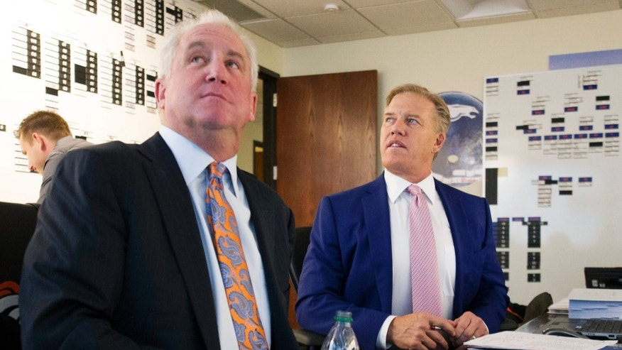 In this photo provided by the Denver Broncos, Broncos vice president John Elway, right, and head coach John Fox watch a broadcast of the NFL football draft in the war room at the team's headquarters in Englewood, Colo., on Thursday, April 25, 2013. Denver has the 28th overall pick the in draft. (AP Photo/Denver Broncos, Eric Bakke)