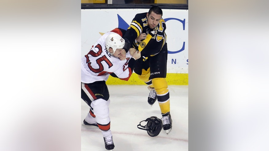 Ottawa Senators right wing Chris Neil (25) and Boston Bruins left wing Milan Lucic (17) fight in the first period of an NHL hockey game in Boston, Sunday, April 28, 2013. (AP Photo/Steven Senne)