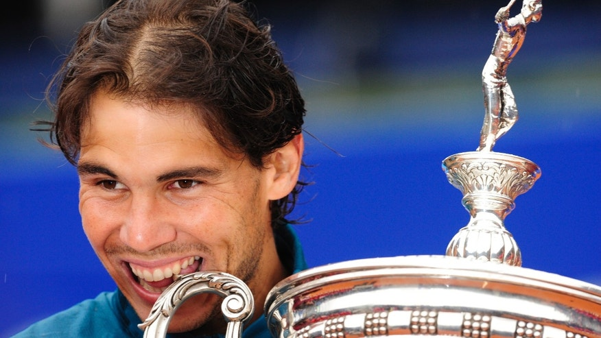 Rafael Nadal of Spain bites the trophy after his victory over Nicolas Almagro during the Barcelona final open tennis in Barcelona, Spain, Sunday, April 28, 2013. Nadal won 6-4, 6-3. (AP Photo/Manu Fernandez)