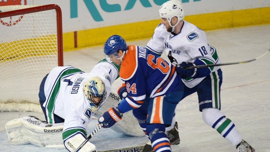 Edmonton Oilers' Nail Yakupov, (64)  tries to score against the Vancouver Canucks goalie Roberto Luongo,(1), with as Canucks' Cam Barker, (18), defends during first period NHL hockey action in Edmonton, on Saturday, April 27, 2013.  (AP Photo/The Canadian Press, Ian Jackson)
