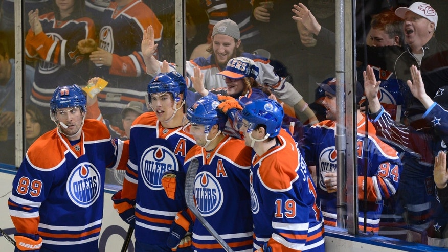 Edmonton Oilers' Sam Gagner, Taylor Hall, Jordan Eberle and Justin Schultz celebrate a goal by Eberle against the Vancouver Canucks during second period NHL hockey action in Edmonton, on Saturday, April 27, 2013. (AP Photo/The Canadian Press, Ian Jackson)