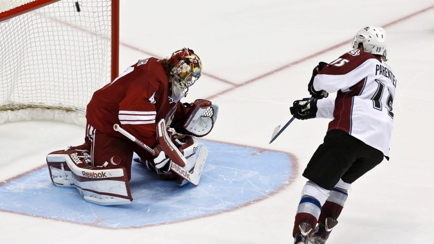Colorado Avalanche's P.A. Parenteau, right, scores the game-winning goal against Phoenix Coyotes' Mike Smith during the shootout in an NHL hockey game, on Friday, April 26, 2013, in Glendale, Ariz.  The Avalanche defeated the Coyotes 5-4 in a shootout. (AP Photo/Ross D. Franklin)