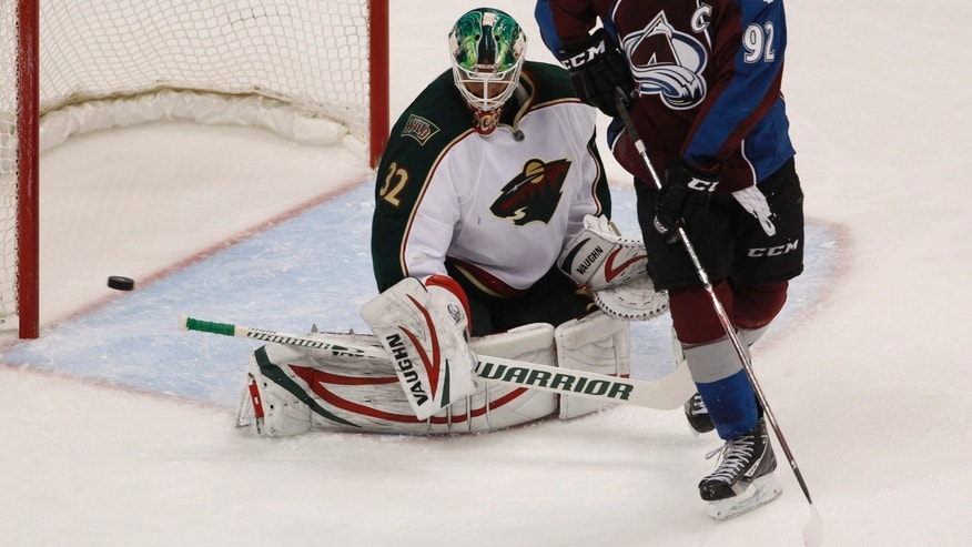 Minnesota Wild goalie Niklas Backstrom, left, of Finland, deflects a shot off the stick of Colorado Avalanche left wing Gabriel Landeskog, of Sweden, in the third period of the Wild's 3-1 victory in an NHL hockey game in Denver on Saturday, April 27, 2013. With the win, the Wild earned the eighth seed in the NHL Western Conference playoffs. (AP Photo/David Zalubowski)