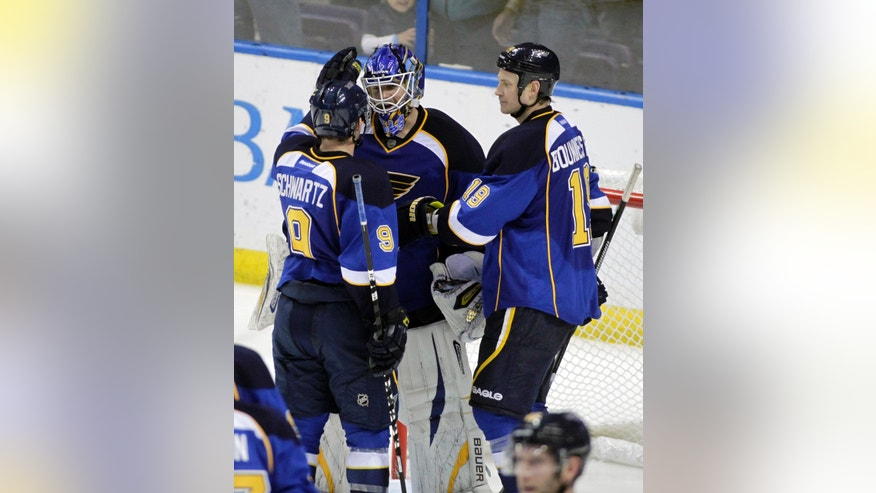 St. Louis Blues goalie Brian Elliott, center, is congratulated by teammates Jaden Schwartz (9) and Jay Bouwmeester (19) after the third period of an NHL hockey game, Saturday, April 27, 2013 in St. Louis. The Blues beat the Blackhawks 3-1. (AP Photo/Tom Gannam)