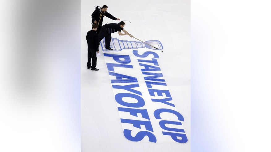 Workers attach a Stanley Cup Playoffs logo onto the ice at TD Garden in Boston, following an NHL hockey game between the Ottawa Senators and the Boston Bruins on Sunday, April 28, 2013. The Senators won 4-2. (AP Photo/Steven Senne)