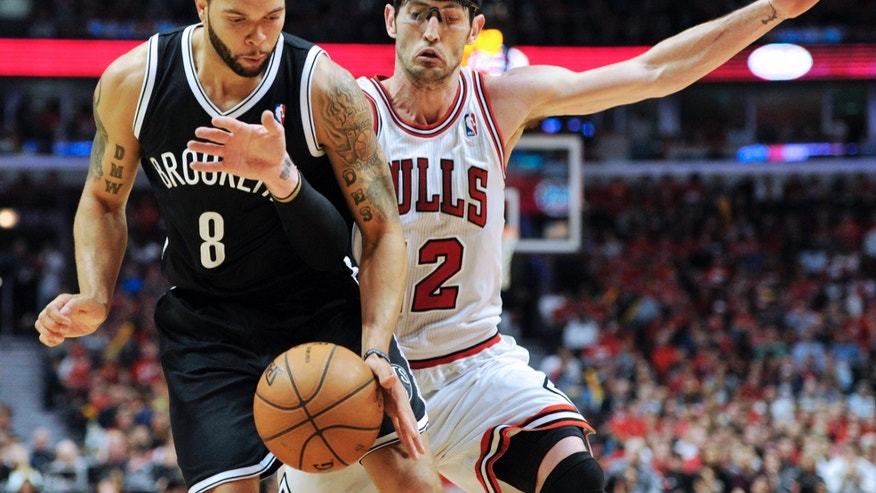 Brooklyn Nets' Deron Williams (8) and Chicago Bulls' Kirk Hinrich (12) scramble for the ball during the second half in Game 4 of their first-round NBA basketball playoff series Saturday, April 27, 2013, in Chicago. The Bulls won 142-134 in three overtimes. (AP Photo/Jim Prisching)