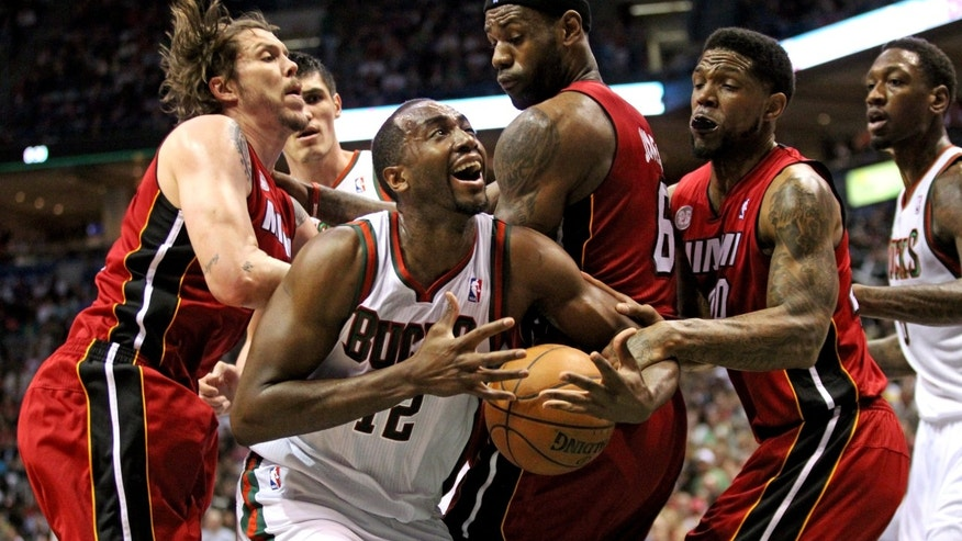 Milwaukee Bucks' Luc Richard Mbah a Moute, second from left, struggles to hold onto the ball around Miami Heat defenders in the third quarter of Game 4 in their first-round NBA basketball playoff series, Sunday, April 28, 2013, in Milwaukee. (AP Photo/The Miami Herald, AL Diaz) MAGS OUT.