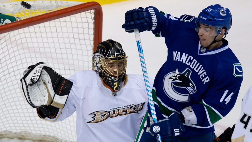 The puck deflects over the net as Anaheim Ducks goalie Jonas Hiller, of Switzerland, and Vancouver Canucks' Alex Burrows look on during the first period of an NHL hockey game in Vancouver, British Columbia, Thursday, April 25, 2013. (AP Photo/The Canadian Press, Darryl Dyck)
