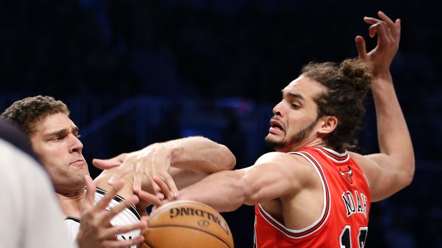 Chicago Bulls center Joakim Noah (13) steals the ball from Brooklyn Nets center Brook Lopez (11) in the first half of Game 5 of their first-round NBA basketball playoff series, Monday, April 29, 2013, in New York. (AP Photo/Kathy Willens)