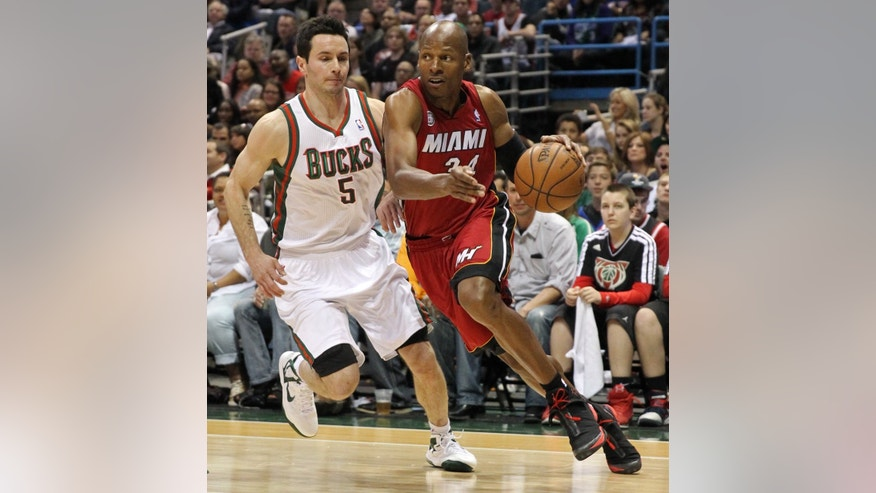 Miami Heat's Ray Allen, right, drives pass the Milwaukee Bucks' J.J. Redick in the first quarter of Game 4 in a first-round NBA basketball game, Sunday, April 28, 2013, in Milwaukee. (AP Photo/The Miami Herald, Al Diaz) MAGS OUT.