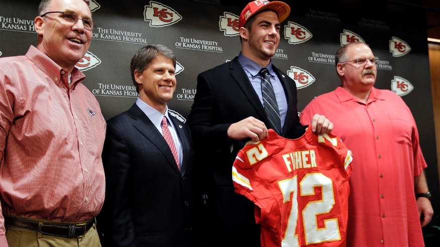 Kansas City Chiefs No. 1 draft pick Eric Fisher, an offensive lineman from Central Michigan, poses with  general manager John Dorsey, left, coach Andy Reid, right, and owner Clark Hunt during an NFL football news conference Friday, April 26, 2013, in Kansas City, Mo. Fisher was the No. 1 overall pick in the NFL draft on Thursday. (AP Photo/Charlie Riedel)