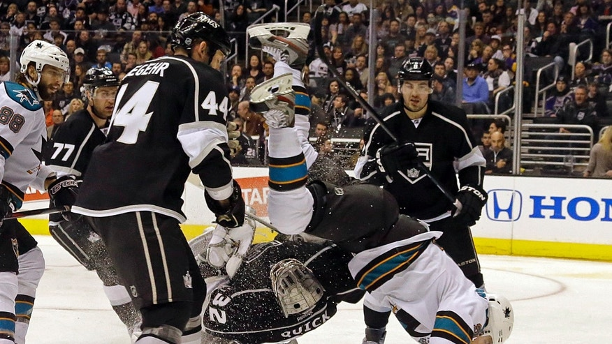 San Jose Sharks left wing T.J. Galiardi goes flying as he tangles with Los Angeles Kings goalie Jonathan Quick and Los Angeles Kings defenseman Robyn Regehr in the third period of an NHL hockey game in Los Angeles Saturday, April 27, 2013. The Kings won, 3-2. (AP Photo/Reed Saxon)