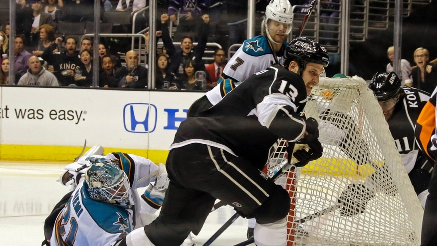 San Jose Sharks goalie Antti Niemi, of Finland, can't block a goal by Los Angeles Kings left wing Dustin Penner, not shown, with Los Angeles Kings left wing Kyle Clifford (13) in the foreground in the second period of an NHL hockey game in Los Angeles Saturday, April 27, 2013. (AP Photo/Reed Saxon)