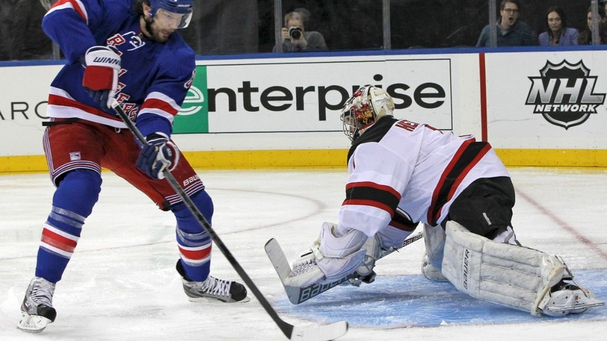 New Jersey Devils goalie Johan Hedberg, right, defends the net against New York Rangers' Anton Stralman, of Sweden, during the second period of the NHL hockey game Saturday, April 27, 2013 at Madison Square Garden in New York.  (AP Photo/Mary Altaffer)
