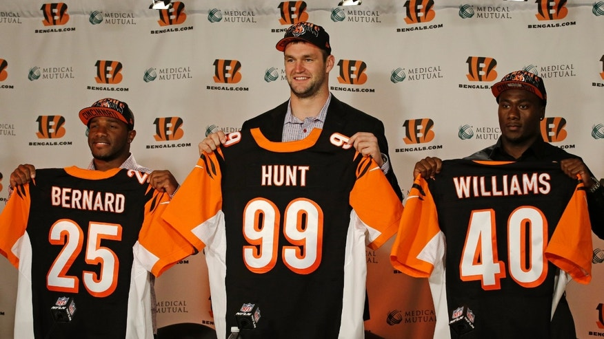 Cincinnati Bengals second-round draft pick Giovani Bernard, a halfback out of North Carolina, (25), second-round draft pick Margus Hunt, a defensive end out of Southern Methodist, (99), and third-round draft pick Shawn Williams, a safety out of Georgia, (40) hold up the numbers they will wear for the NFL football team as they were introduced at a press conference, Saturday, April 27, 2013, in Cincinnati. (AP Photo/Al Behrman)