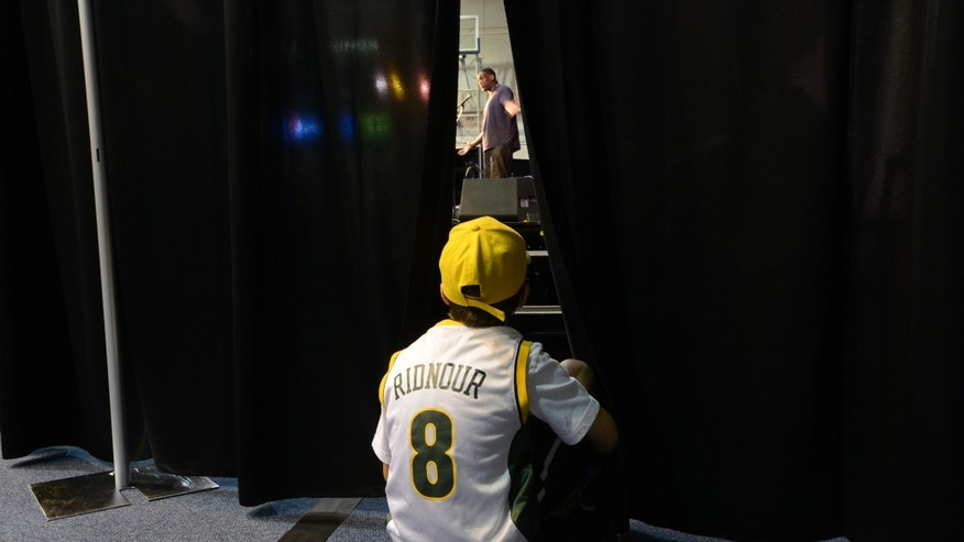 "In this photo taken Saturday, April 27, 2013, Carson Wisbey, 8, finds an opening in a side curtain to watch and listen to former SuperSonics NBA basketball player Shawn Kemp speak at a ""Sonics All Day"" rally held at Western Washington University. The NBA's relocation committee voted unanimously Monday, April 29, 2013, to recommend that NBA owners reject the application for the Sacramento Kings to relocate to Seattle and the NBA Board of Governors will vote on the matter May 13, 2013. (AP Photo/The Bellingham Herald, Andy Bronson)"