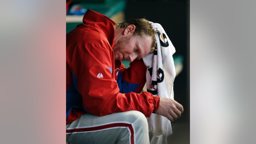 Philadelphia Phillies starting pitcher Roy Halladay wipes his head in the dugout in the fourth inning of a baseball game against the Cleveland Indians, Tuesday, April 30, 2013, in Cleveland.  (AP Photo/Tony Dejak)