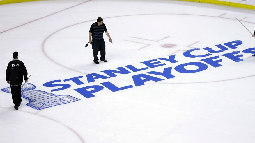 Workers position a Stanley Cup Playoffs logo onto the ice at TD Garden in Boston, following an NHL hockey game between the Ottawa Senators and the Boston Bruins on Sunday, April 28, 2013. The Senators won 4-2. (AP Photo/Steven Senne)