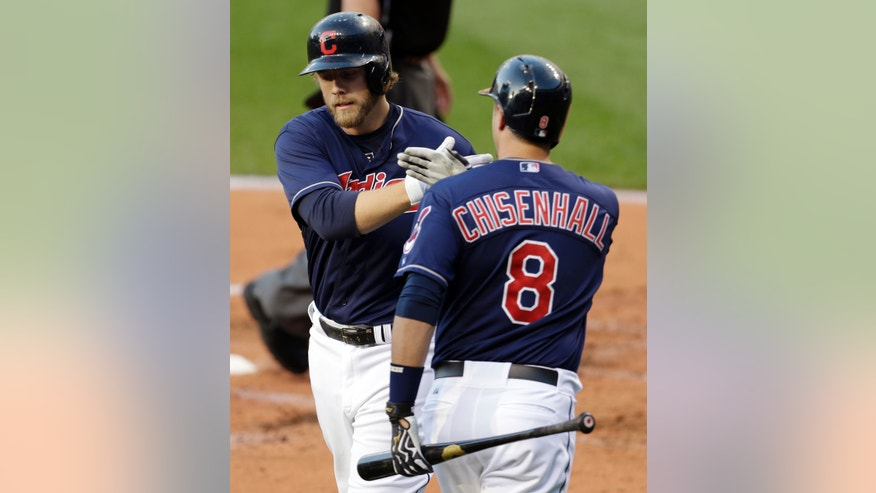 Cleveland Indians' Mark Reynolds, left, is congratulated by Lonnie Chisenhall after Reynolds hit a two-run home run off Philadelphia Phillies starting pitcher Roy Halladay during the first inning of a baseball game, Tuesday, April 30, 2013, in Cleveland. Jason Giambi also scored. (AP Photo/Tony Dejak)