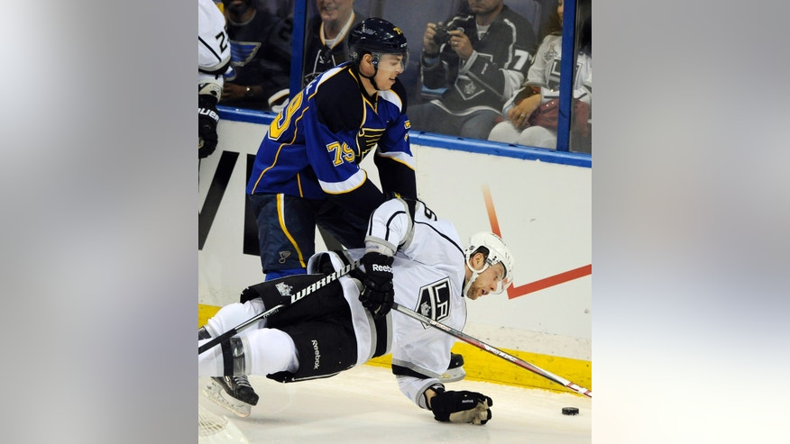 St. Louis Blues' Adam Cracknell (79) and  Los Angeles Kings' Jake Muzzin, right, compete for the puck during the second period of Game 1 of their first-round NHL hockey Stanley Cup playoff series, Tuesday, April 30, 2013, in St. Louis. (AP Photo/Bill Boyce)