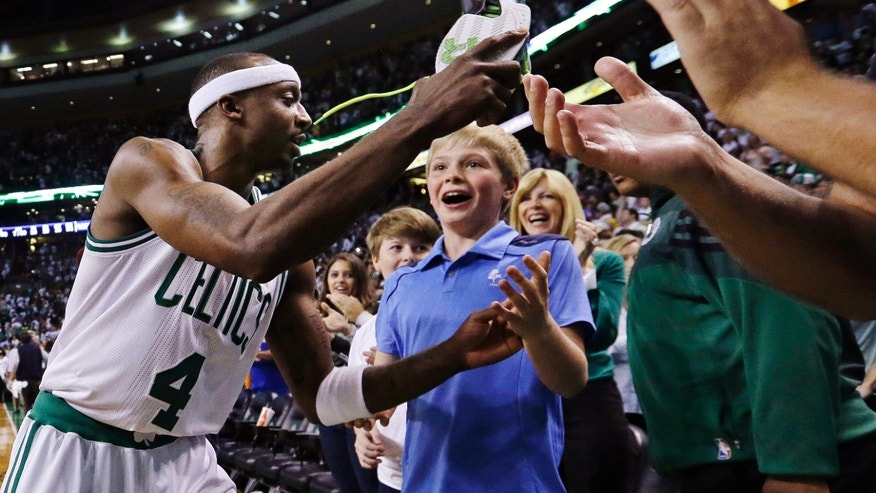Boston Celtics guard Jason Terry gives his sneakers to fans as he leaves the court following their 97-90 win over the New York Knicks in overtime of Game 4 of a first-round NBA basketball playoff series in Boston, Sunday, April 28, 2013. (AP Photo/Elise Amendola)