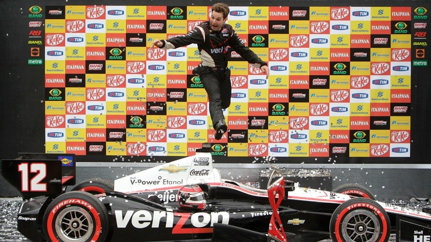 FILE - In this April 29, 2012 file photo, IndyCar driver Will Power, of Australia, jumps off his car at the winner's podium as he celebrates winning the the IndyCar Sao Paulo 300 in Sao Paulo, Brazil. On the one-year anniversary of his last victory, Power heads back to Brazil for the Sao Paulo 300, a race he has won every time since it was added to the calendar in 2010.  (AP Photo/Andre Penner, File)