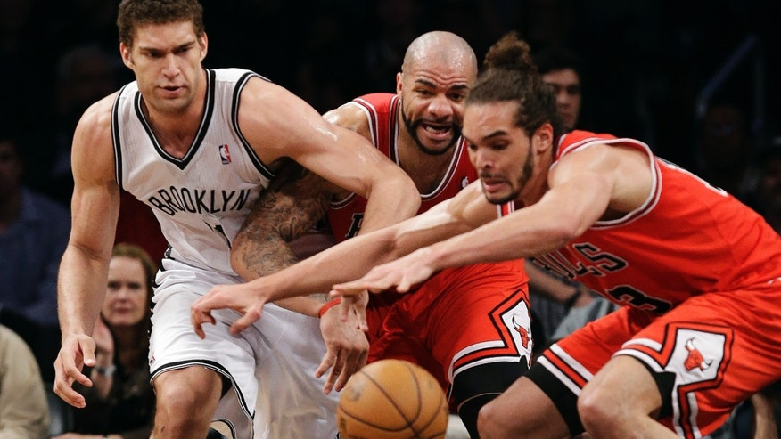Brooklyn Nets center Brook Lopez (11), Chicago Bulls forward Carlos Boozer, center, and center Joakim Noah, right, compete for a loose ball in the first half of Game 5 of their first-round NBA basketball playoff series, Monday, April 29, 2013, in New York. (AP Photo/Kathy Willens)