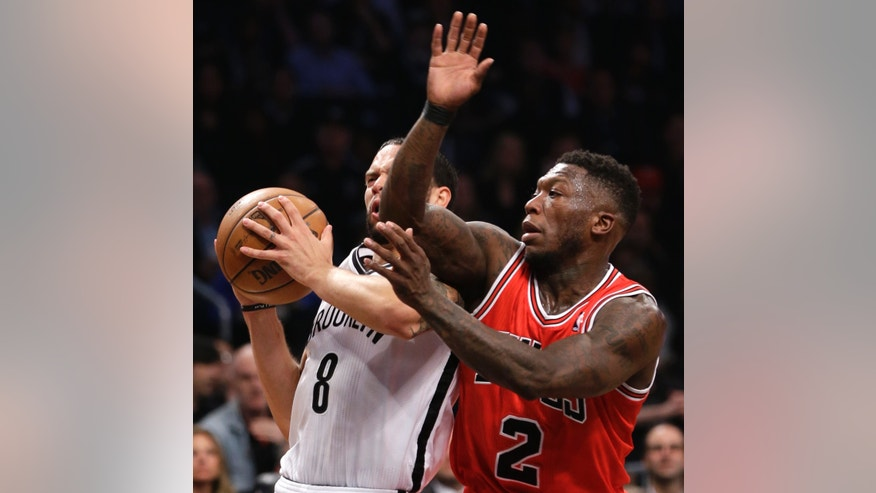 Brooklyn Nets guard Deron Williams (8) collides with Chicago Bulls guard Nate Robinson (2) as he drives toward the basket in the first half of Game 5 of their first-round NBA basketball playoff series, Monday, April 29, 2013, in New York. (AP Photo/Kathy Willens)