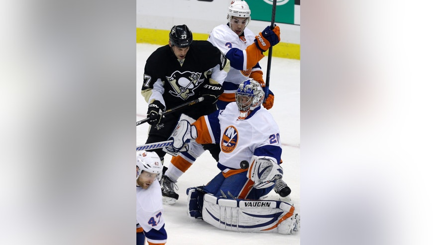 New York Islanders goalie Evgeni Nabokov (20) can't glove a rebound in front of Pittsburgh Penguins' Craig Adams and New York Islanders' Travis Hamonic (3) during the first period of Game 1 of an NHL hockey Stanley Cup first-round playoff series, Wednesday, May 1, 2013, in Pittsburgh. (AP Photo/Gene J. Puskar)