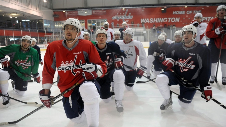 Washington Capitals Alex Ovechkin of Russia, second from left, and his teammates listen to coach Adam Oates during NHL hockey team practice at the Kettler Capitals Iceplex in Arlington, Va. Wednesday, May 1, 2013. The Capitals host the New York Rangers in Game 1 of a first-round NHL hockey Stanley Cup playoff series on Thursday. (AP Photo/Susan Walsh)