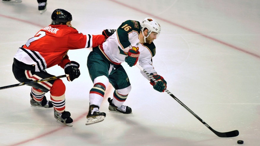 Chicago Blackhawks' Brent Seabrook checks the Minnesota Wild's Jason Zucker (16) as he handles the puck during the first period of Game 1 of an NHL hockey Stanley Cup playoff series, Tuesday, April 30, 2013, in Chicago. (AP Photo/Jim Prisching)