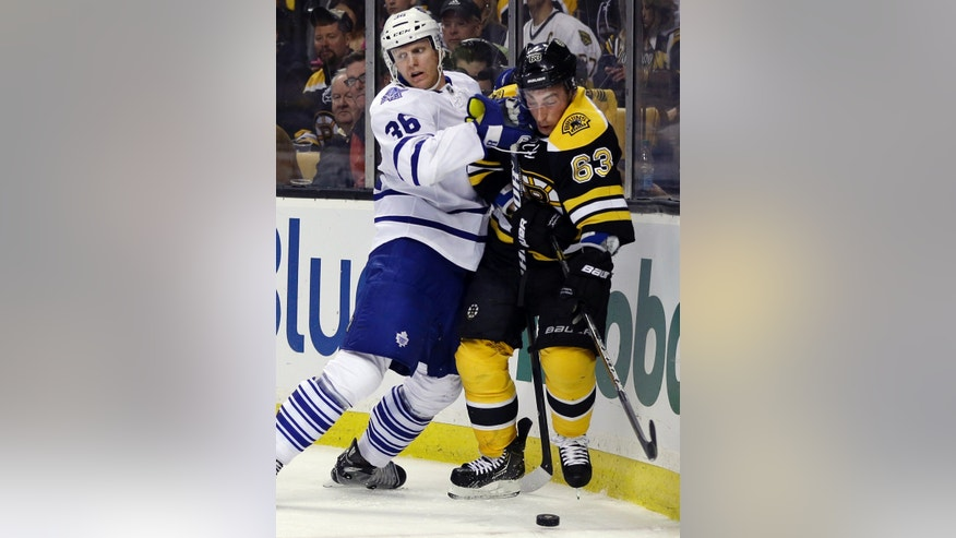 Toronto Maple Leafs defenseman Carl Gunnarsson (36) and Boston Bruins left wing Brad Marchand (63) grapple along the boards for the puck during the second period in Game 1 of a first-round NHL hockey playoff series in Boston, Wednesday, May 1, 2013. (AP Photo/Elise Amendola)