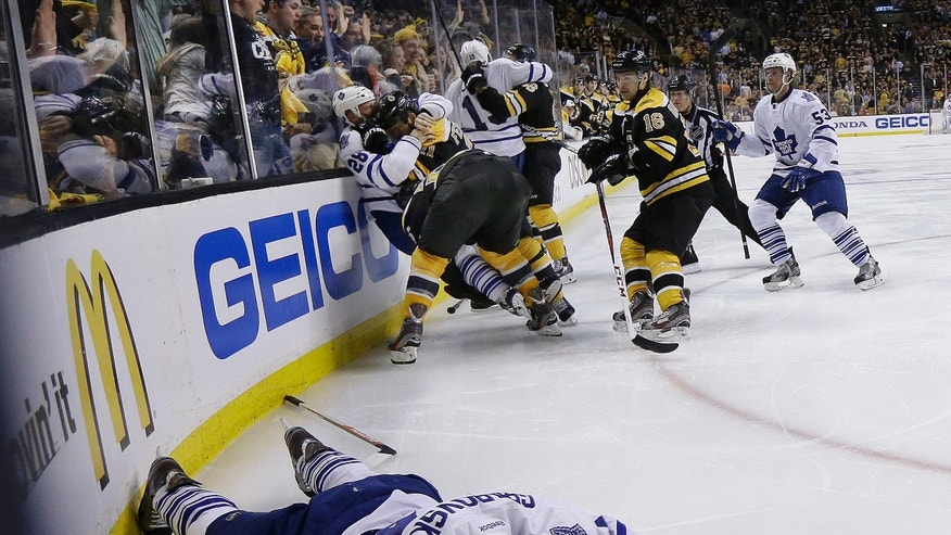 Toronto Maple Leafs center Mikhail Grabovski (84) lies on the ice after a hard hit as Boston Bruins and Maple Leafs players grapple behind during the third period in Game 1 of a first-round NHL hockey playoff series in Boston, Wednesday, May 1, 2013. (AP Photo/Elise Amendola)