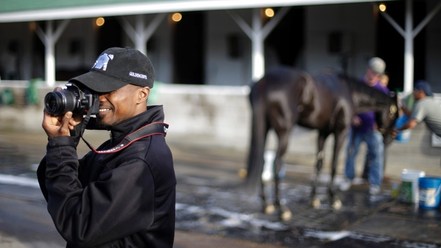 Kentucky Derby entrant Goldencents jockey Kevin Krigger takes pictures outside his stable at Churchill Downs Thursday, May 2, 2013, in Louisville, Ky. Saturday will be the 139th running of the Kentucky Derby. (AP Photo/David Goldman)